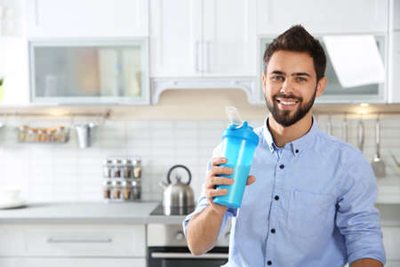 Young man holding bottle of protein shake in kitchen. Space for text Stock Photo