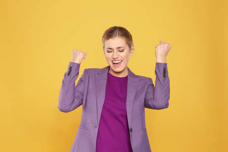 Happy young businesswoman celebrating victory on color background Imagens - 114903038