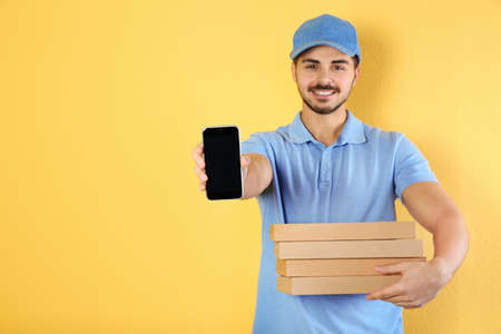 Young man holding pizza boxes and smartphone on on color background, mockup for design. Online food delivery