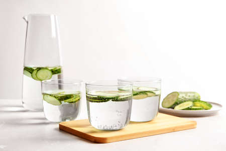 Glasses and jug of fresh cucumber water on table Stock fotó