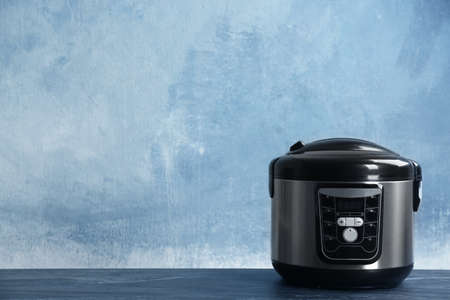 Modern powerful multi cooker on table against color background. Space for text