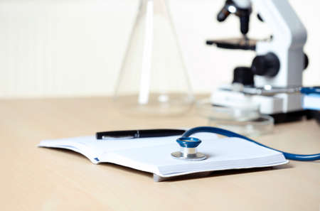 Stethoscope with notepad and pen on table. Medical students stuff