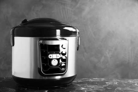 Modern powerful multi cooker on table against grey background. Space for text