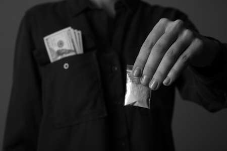 Drug dealer holding bag with cocaine on dark background, closeup. Black and white effect Standard-Bild