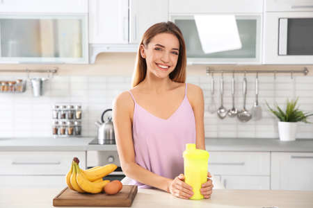 Young woman holding bottle of protein shake at table with ingredients in kitchen 免版税图像