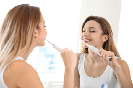 Young beautiful woman with toothbrush near mirror in bathroom. Personal hygiene Banco de Imagens - 115076547