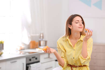 Young woman choosing between orange and donut in kitchen, space for text. Healthy diet Stock Photo