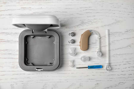Flat lay composition with hearing aid and accessories on white wooden background