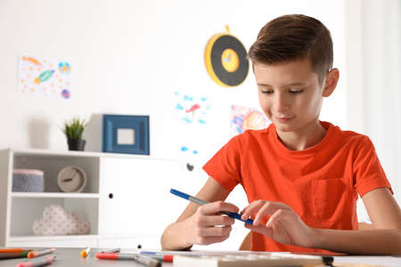 Little child drawing picture at table in room. Space for text Фото со стока - 115076599