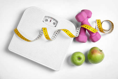 Composition with scales, apples, tape measure and dumbbells on white background, top view