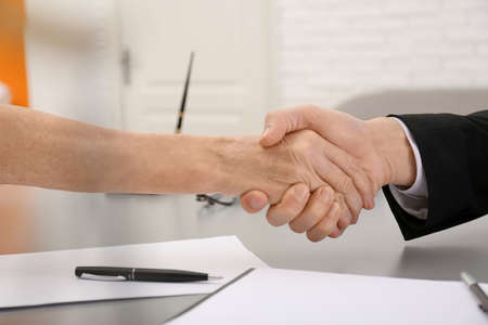 Lawyer shaking hands with client in office, closeup