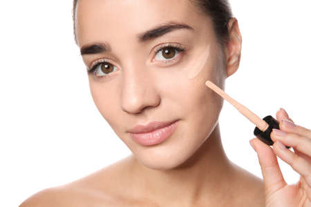 Young woman applying foundation on her face against white background Stockfoto