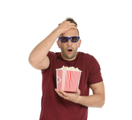 Emotional man with 3D glasses and popcorn during cinema show on white background