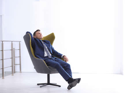 Young businessman sitting in comfortable armchair indoors. Space for text 스톡 콘텐츠
