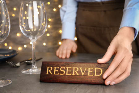 Waiter setting RESERVED sign on restaurant table, closeup