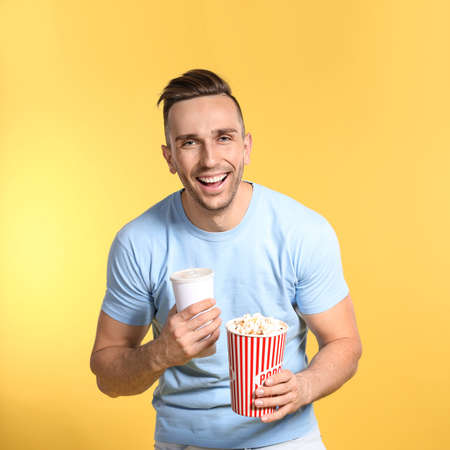 Man with popcorn and beverage during cinema show on color background 스톡 콘텐츠