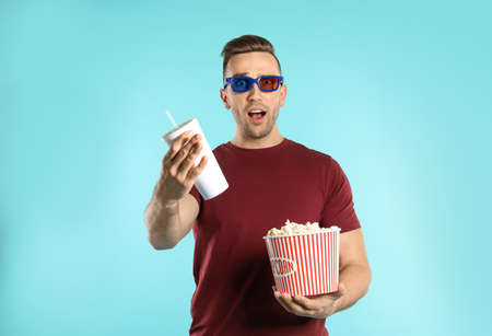 Emotional man with 3D glasses, popcorn and beverage during cinema show on color background Stock Photo