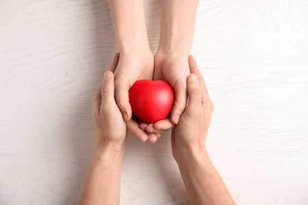 People holding red heart on wooden background, top view. Cardiology concept 免版税图像