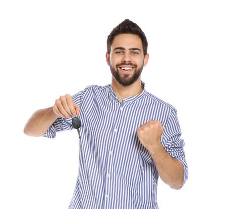 Happy young man with car key on white background. Getting driving license