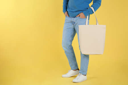 Young man holding textile bag on color background, closeup. Mockup for design Фото со стока