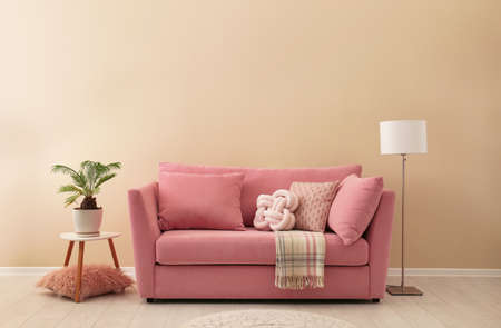 Simple living room interior with modern sofa near color wall. Space for text 스톡 콘텐츠
