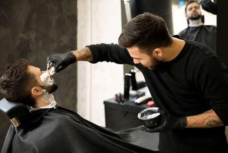 Professional hairdresser applying shaving foam onto client's skin in barbershop