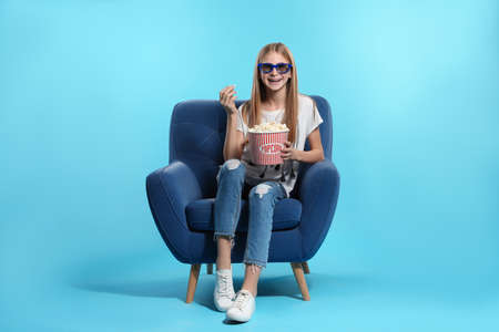 Teenage girl with 3D glasses and popcorn sitting in armchair during cinema show on color background 免版税图像