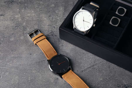 Composition with stylish wrist watches on gray table. Fashion accessory