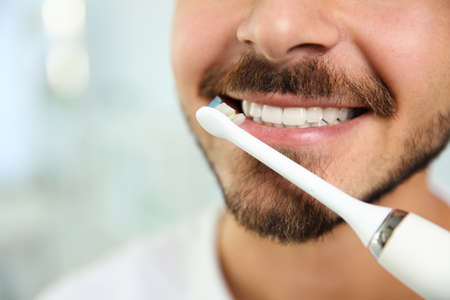 Young man with electric toothbrush on blurred background, closeup. Space for text Фото со стока