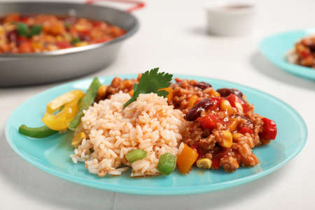 Chili con carne served with rice on table