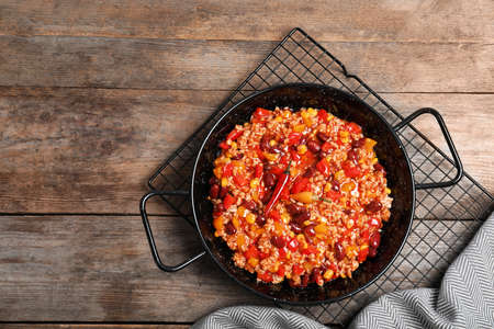 Dish with chili con carne on wooden background, top view. Space for text