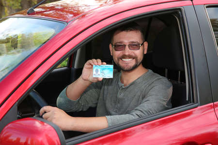Happy man showing driving license from car