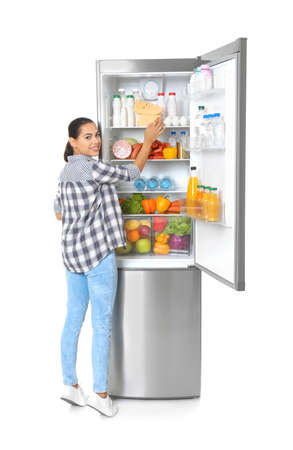 Young woman near open refrigerator on white background