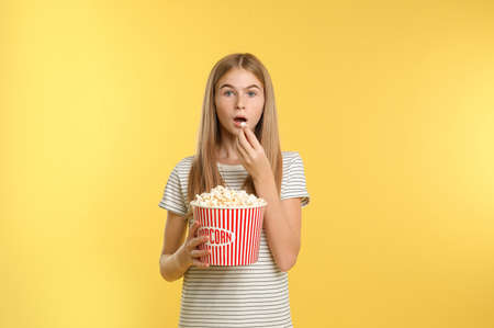 Emotional teenage girl with popcorn during cinema show on color background