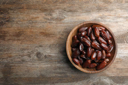 Bowl of sweet dates on wooden background, top view with space for text. Dried fruit as healthy snack