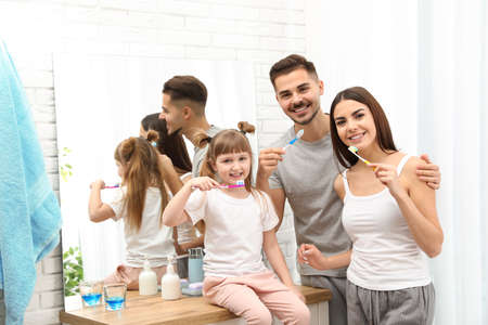 Little girl and her parents brushing teeth together in bathroom at home. Space for text Stock Photo