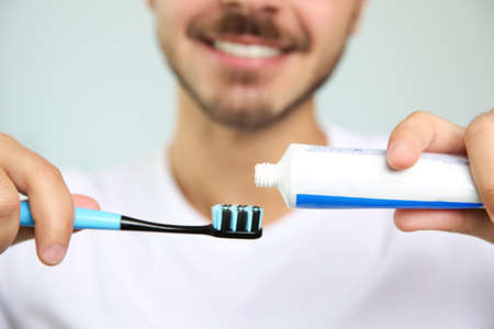 Man with toothbrush and paste on blurred background, closeup