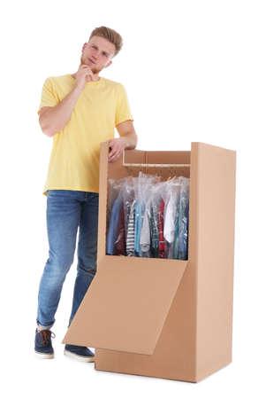 Young emotional man near wardrobe box on white background