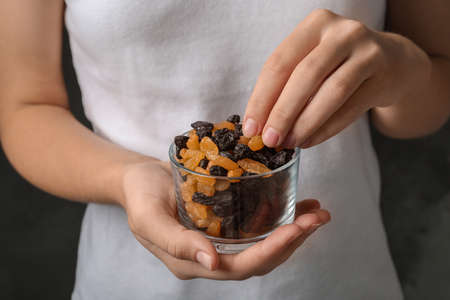 Woman holding glass with raisins on black background, closeup