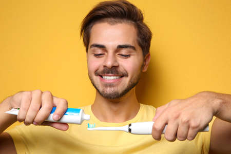 Portrait of young man with electric toothbrush and paste on color background Imagens