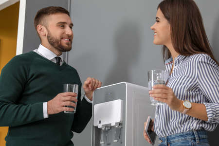 Employees having break near water cooler in office