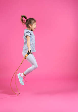 Active girl jumping rope on color background 写真素材