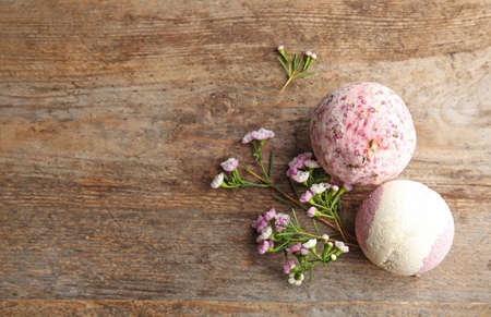 Flat lay composition with bath bombs, flowers and space for text on wooden background