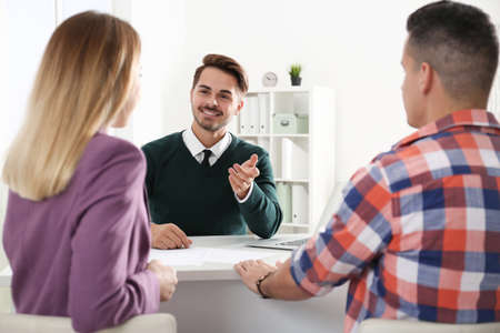 Real estate agent consulting young couple in office