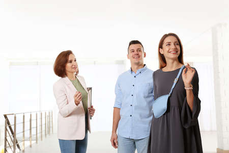 Real estate agent showing new apartment to young couple 写真素材