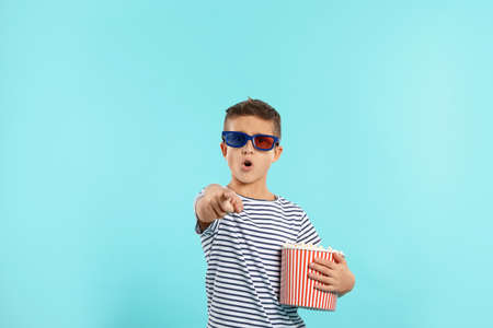 Emotional boy with 3D glasses and popcorn during cinema show on color background