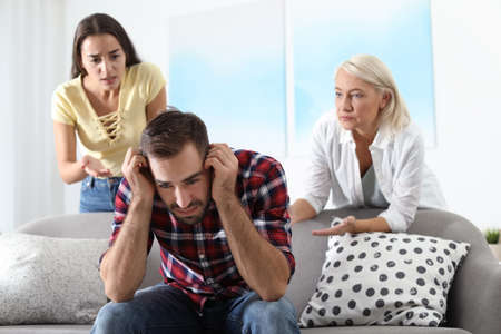 Young man having argument with wife and mother-in-law at home. Family quarrel