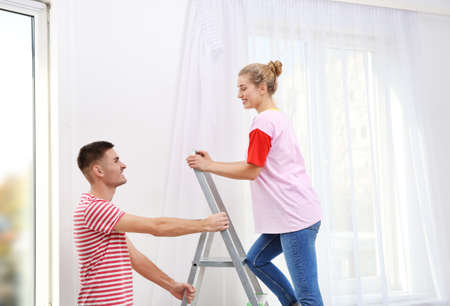 Young couple hanging window curtain indoors. Interior decor element