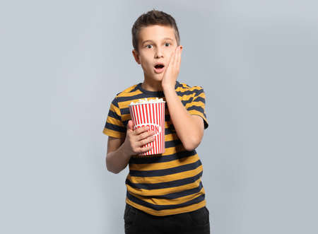 Emotional boy with popcorn during cinema show on grey background Stock Photo