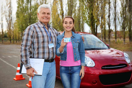 Senior instructor and happy woman with driving license outdoors